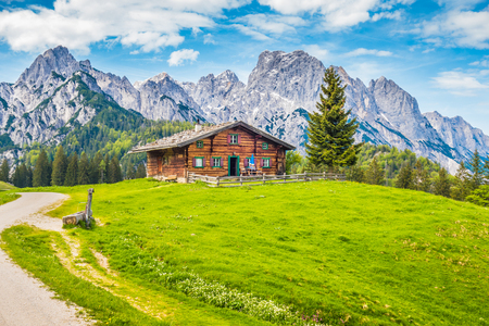 Foto de Panoramic view of idyllic mountain scenery in the Alps with traditional mountain chalet and fresh green mountain pastures with blooming flowers on a sunny day with blue sky and clouds in summer - Imagen libre de derechos