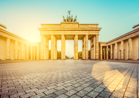 Photo for Famous Brandenburger Tor (Brandenburg Gate), one of the best-known landmarks and national symbols of Germany, in beautiful golden morning light at sunrise with lens flare effect, Berlin, Germany - Royalty Free Image