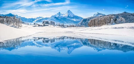 Photo pour Panoramic view of beautiful white winter wonderland scenery in the Alps with snowy mountain summits reflecting in crystal clear mountain lake on a cold sunny day with blue sky and clouds - image libre de droit