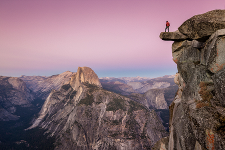 Photo pour A fearless male hiker is standing on an overhanging rock at Glacier Point enjoying the breathtaking view towards famous Half Dome in beautiful post sunset twilight in summer, Yosemite National Park, California - image libre de droit