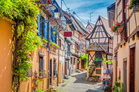 Foto de Charming street scene with colorful houses in the historic town of Eguisheim on a beautiful sunny day with blue sky and clouds in summer, Alsace, France - Imagen libre de derechos