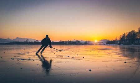 Photo for Scenic panoramic view of the silhouette of a young hockey player skating on a frozen lake with amazing reflections in beautiful golden evening light at sunset in winter - Royalty Free Image