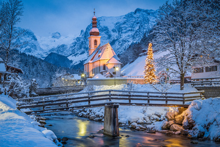 Foto de Beautiful twilight view of Sankt Sebastian pilgrimage church with decorated Christmas tree illuminated during blue hour at dusk in winter, Ramsau, Nationalpark Berchtesgadener Land, Bavaria, Germany - Imagen libre de derechos