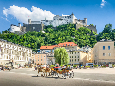 Foto de Beautiful panoramic view of the historic city of Salzburg with traditonal horse-drawn Fiaker carriage and famous Hohensalzburg Fortress on a hill on a sunny day with blue sky and clouds in summer - Imagen libre de derechos