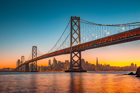Photo pour Classic panoramic view of San Francisco skyline with famous Oakland Bay Bridge illuminated in beautiful golden evening - image libre de droit