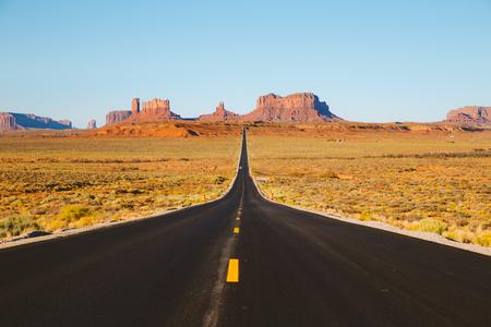 Foto de Classic panorama view of historic U.S. Route 163 running through famous Monument Valley in beautiful golden evening light at sunset in summer, Utah, USA - Imagen libre de derechos