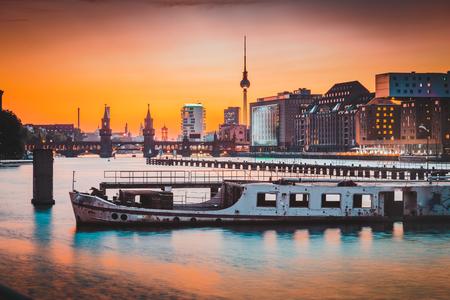 Foto de Panoramic view of Berlin skyline with famous TV tower and Oberbaum Bridge with old ship wreck lying in river Spree at dusk, Berlin Friedrichshain-Kreuzberg, Germany. - Imagen libre de derechos
