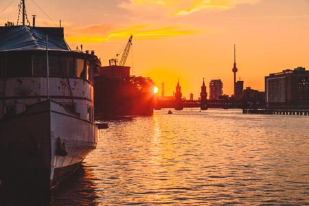 Foto de Panoramic view of Berlin skyline with famous TV tower and Oberbaum Bridge with old ship wreck lying in river Spree at dusk, Berlin Friedrichshain-Kreuzberg, Germany. - Imagen libre de derechos