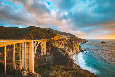 Foto de Scenic panoramic view of historic Bixby Creek Bridge along world famous Highway 1 in beautiful golden evening light at sunset with dramatic cloudscape in summer, Monterey County, California, USA - Imagen libre de derechos
