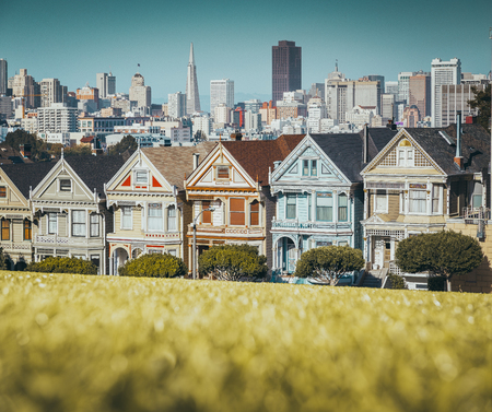 Photo pour Classic postcard view of famous Painted Ladies, a row of colorful Victorian houses located at Alamo Square, with the skyline of San Francisco in the background - image libre de droit