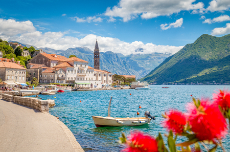 Foto de Scenic panorama view of the historic town of Perast at famous Bay of Kotor with blooming flowers on a beautiful sunny day with blue sky and clouds in summer, Montenegro, southern Europe - Imagen libre de derechos