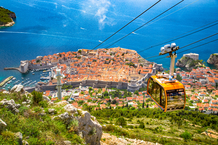 Foto de Aerial panoramic view of the old town of Dubrovnik with famous Cable Car on Srd mountain on a sunny day with blue sky and clouds in summer, Dalmatia, Croatia - Imagen libre de derechos