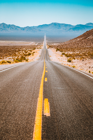 Photo pour Classic panorama view of an endless straight road running through the barren scenery of the American Southwest with extreme heat haze on a beautiful sunny day with blue sky in summer - image libre de droit