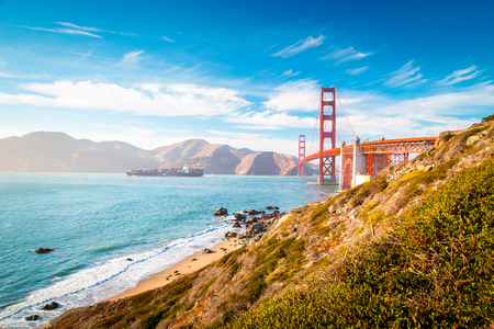 Foto per Classic view of famous Golden Gate Bridge with cargo ship on a sunny day with blue sky and clouds in summer, San Francisco, California, USA - Immagine Royalty Free