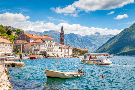 Foto de Scenic panorama view of the historic town of Perast located at world-famous Bay of Kotor on a beautiful sunny day with blue sky and clouds in summer, Montenegro, southern Europe - Imagen libre de derechos