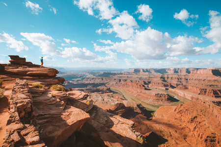 Photo pour A young hiker is standing on the edge of a cliff enjoying a dramatic overlook of famous Colorado River and beautiful Canyonlands National Park in scenic Dead Horse Point State Park, Utah, USA - image libre de droit