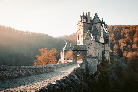 Photo pour Beautiful view of famous Eltz Castle in scenic golden morning light at sunrise with blue sky on a sunny day in fall with retro vintage VSCO style filter effect, Wierschem, Rheinland-Pfalz, Germany - image libre de droit