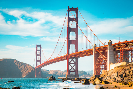Photo for Classic view of famous Golden Gate Bridge in beautiful golden evening light on a sunny day with blue sky and clouds in summer, San Francisco, California, USA - Royalty Free Image