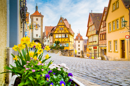 Photo for Classic view of the medieval town of Rothenburg ob der Tauber with blooming flowers on a beautiful sunny day with blue sky and clouds in springtime, Bavaria, Germany - Royalty Free Image