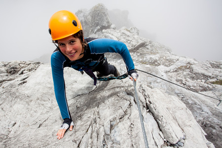 Photo pour Young woman climbing steep rock wall - image libre de droit