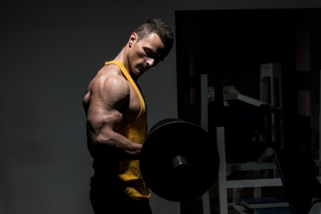 Photo pour young man doing heavy weight exercise for biceps - image libre de droit