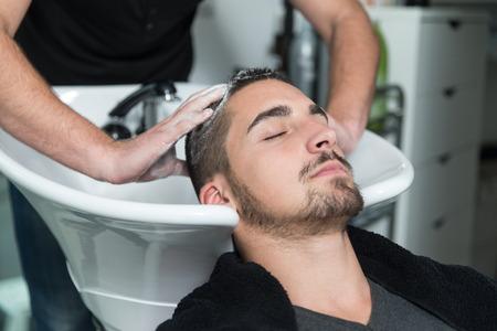 Foto de Hairstylist Hairdresser Washing Customer Hair - Young Man Relaxing In Hairdressing Beauty Salon - Imagen libre de derechos