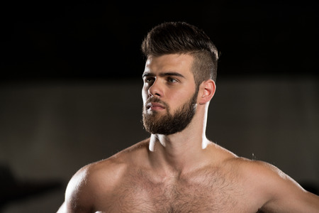Foto de Portrait Of A Young Sporty Man In The Modern Gym With Exercise Equipment - Imagen libre de derechos