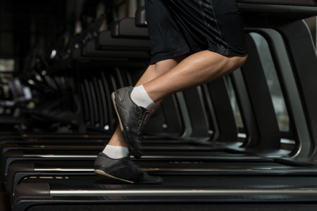 Photo for Close Up Of Male Legs Running On Treadmill - Blurred Motion - Royalty Free Image
