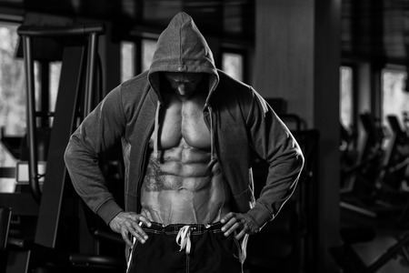 Photo pour Portrait Of A Physically Fit Man In Hoodie - In Modern Fitness Center - Showing His Six Pack - Black And White Photo - image libre de droit