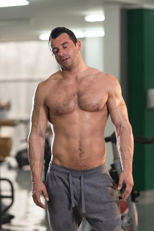 Foto de Portrait of a Tired Muscular Man Standing in Health Club - Imagen libre de derechos
