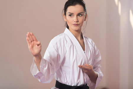 Photo for Young Woman Practicing Her Karate Moves - White Kimono - Black Belt - Royalty Free Image
