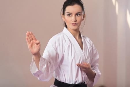Foto de Young Woman Practicing Her Karate Moves - White Kimono - Black Belt - Imagen libre de derechos