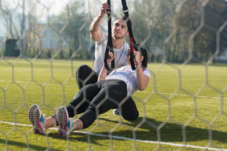 Photo pour Young Couple Doing Crossfit With Trx Fitness Straps in City Park Area - Training and Exercising for Endurance - Healthy Lifestyle Concept Outdoor - image libre de droit