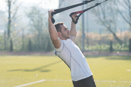 Photo pour Attractive Man Doing Crossfit With Trx Fitness Straps in City Park Area - Training and Exercising for Endurance - Healthy Lifestyle Concept Outdoor - image libre de droit