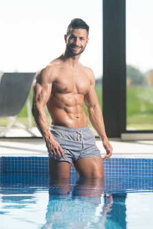 Photo for Young Healthy Good Looking Macho Man Model Athlete At Hotel Indoor Pool - Royalty Free Image