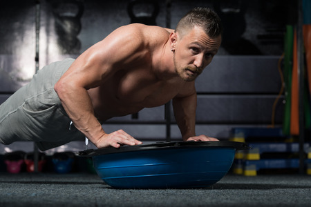 Photo for Personal Trainer Doing Pushups On Floor With Bosu Balance Ball As Part Of Bodybuilding Training - Royalty Free Image