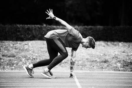 Photo for Athletic Man on Running Track Getting Ready to Start Run - Royalty Free Image