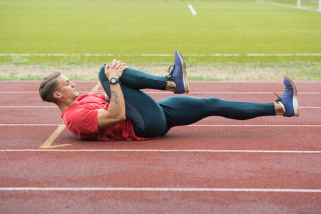 Photo for Young Athlete Man Relax and Strech Ready for Run at Athletics Race Track on Stadium - Royalty Free Image