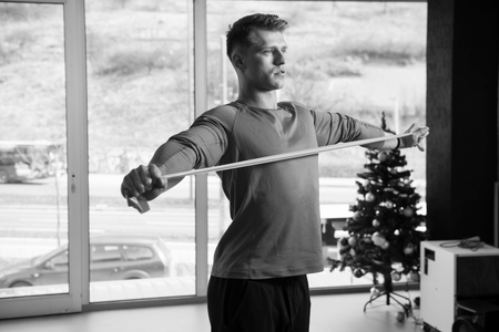 Photo for Athlete in Sport Sportswear Workout With Elastic Resistance Band - Doing Shoulder Or Back Exercises in Gym - Royalty Free Image