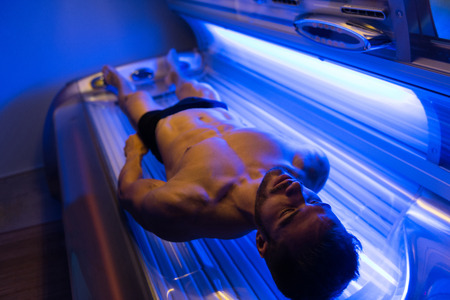 Photo for Young Muscular Man At Solarium In Beauty Salon - Royalty Free Image