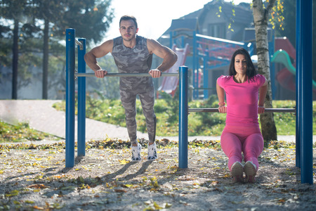 Photo pour Young Couple Doing Crossfit Exercise With Dips Bar in City Park Area - Training and Exercising for Endurance - Healthy Lifestyle Concept Outdoor - image libre de droit