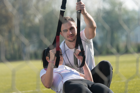 Photo pour Attractive Couple Doing Crossfit With Fitness Straps in City Park Area - Training and Exercising for Endurance - Healthy Lifestyle Concept Outdoor - image libre de droit
