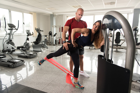 Photo pour Couple Athlete in Sport Sportswear Workout With Elastic Resistance Band - Doing Legs Exercises in Gym - image libre de droit