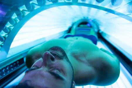 Photo pour Young Muscular Man At Solarium In Beauty Salon - image libre de droit