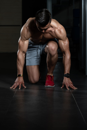 Photo for Strong Muscular Men Kneeling On The Floor - Almost Like Sprinter Starting Position - Royalty Free Image