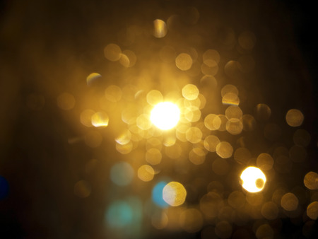 Photo pour abstract black background, gold bubble lights or snowflakes falling at night. Bokeh Christmas background with circle designs or blurred stars shining, glitter magic background - image libre de droit