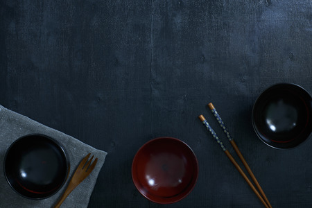 Black color wooden table top view. On the table are the Japanese wooden spoon, chopsticks, bowl and table linen.