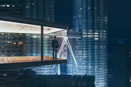 Photo for Businessman in an modern sky office by night with beautiful city skyline view . - Royalty Free Image