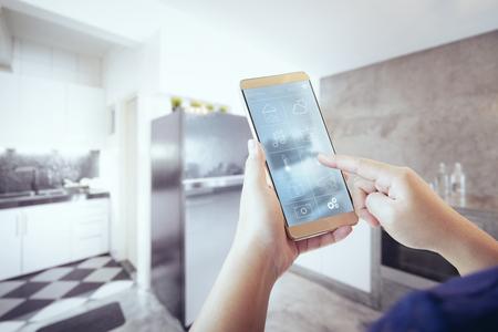 Foto de Unknown woman hand using remote home control system on phone. - Imagen libre de derechos