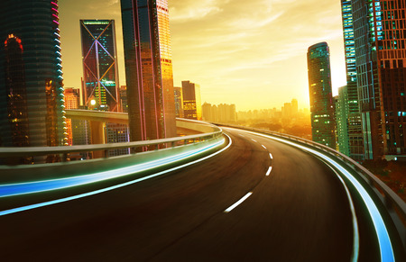 Photo pour Highway overpass motion blur with city skyline and urban skyscrapers , sunset and twilight scene. - image libre de droit